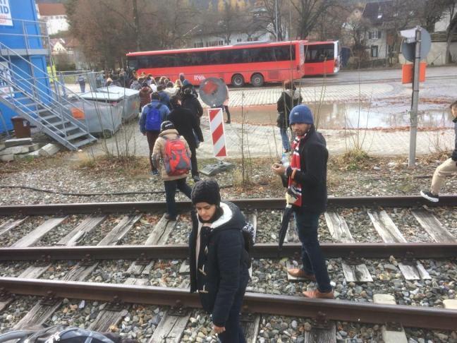 Passageiros atravessam a linha para pegar o ônibus
